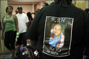 A photo of Keondra Hooks, 1, is on the back of a mourner during the funeral  last August for the little girl who died after being shot inside Moody Manor.