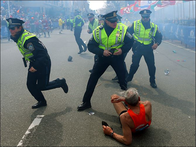 APTOPIX Boston Marathon Explosions Iffrig Bill Iffrig, 78, lies on the ground as police officers react to a second explosion at the finish line of the Boston Marathon in Boston, Monday. Iffrig, of Lake Stevens, Wash., was running his third Boston Marathon and near the finish line when he was knocked down by one of two bomb blasts.