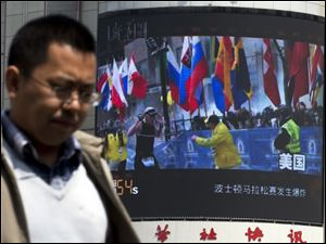 A Chinese man walks past a huge screen which reports Boston Marathon bombings that killed three and wounded more than 170 people, in Beijing, China today.