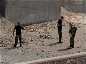Israeli security investigates the scene of a rocket attack in Eilat, Israel, today.