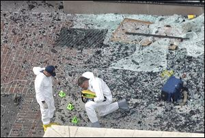Two men in hazardous materials suits put numbers on the shattered glass and debris as they investigated the scene Tuesday at the first bombing on Boylston Street in Boston.