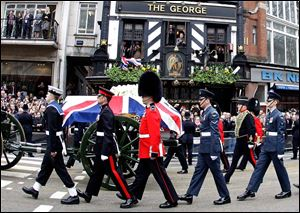 A Union flag draped coffin bearing the body of former British Prime Minister Margaret Thatcher is carried on a gun carriage drawn by the King's Troop Royal Artillery during her ceremonial funeral procession in London, Wednesday.