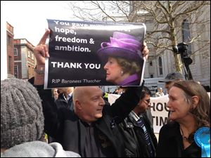 A supporter of former Prime Minister Margaret Thatcher holds up a sign thanking her for her service to the United Kingdom.