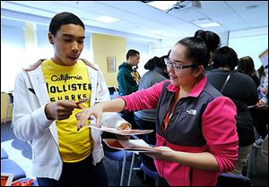 Start High seniors Marcus Johnson and Maria Parraz play a bingo game that aims to get students to learn about one another at the Latino Issues Conference at Bowling Green State University.