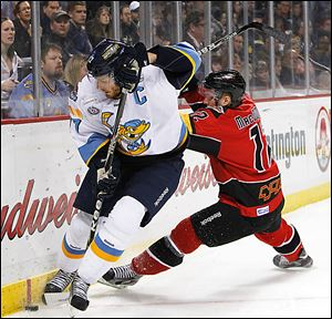 Toledo's Kyle Rogers, left, battles for the puck with Cincinnati's David MacDonald. The Walleye made the playoffs for the first time since 2010 but lost in the first round again.