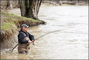 Greg Pauken of Maumee fishes close to the shoreline in the Maumee River at Side Cut Metropark. High water from recent rain adds a challenge to walleye fishing.