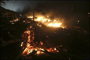 The remains of a home burn early Thursday morning after a fertilizer plant exploded Wednesday night in West, Texas.