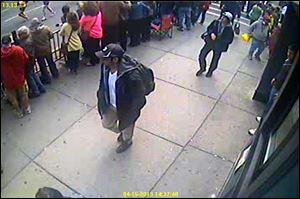 A surveillance image released by the FBI of the Boston Marathon bombing suspects, a man in a black baseball cap and the man behind him on the sidewalk in a white cap.