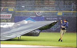 A member of the Toledo Mud Hens grounds crew pulls the tarp to cover the field as play is called during the top of the fifth inning.