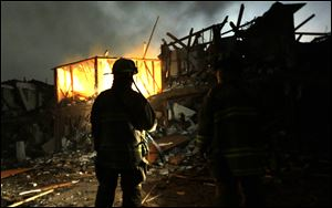 Firefighters use flashlights to search a destroyed apartment complex near a fertilizer plant that exploded.