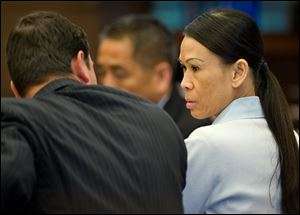 Catherine Kieu sits next to her attorney, deputy public defender, Frank Bittar, before opening statements Wednesday, April 17, 2013 in Santa Ana, Calif.