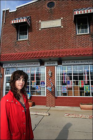 Wendy Beallas, owner of  Flag Sales and Repairs on North Summit Street in Point Place, is concerned about the difficulty of removing the paint from the 86-year-old former fire station. She wants the teenager arrested in the incident to remove the graffiti.  The business, founded by her late father, has been located in the brick structure for 14 years.