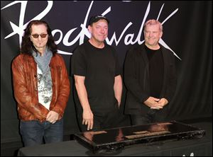 Members of the band Rush are, from left, Geddy Lee, Neil Peart, and Alex Lifeson. They are among the 2013 group of Rock and Roll Hall of Fame inductees.