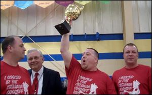 Shawn Zaborski hoists the trophy as winner of the 2013 Polish-American Community of Toledo's Kielbasa Cook-off, making his team, Polish Village Kielbasa, the 'Kielbasa King' for the year. Celebrating with him are, from left, Ladden Vernon; Stan Machosky, president of the PACT board of directors, and Eric Smigelski.
