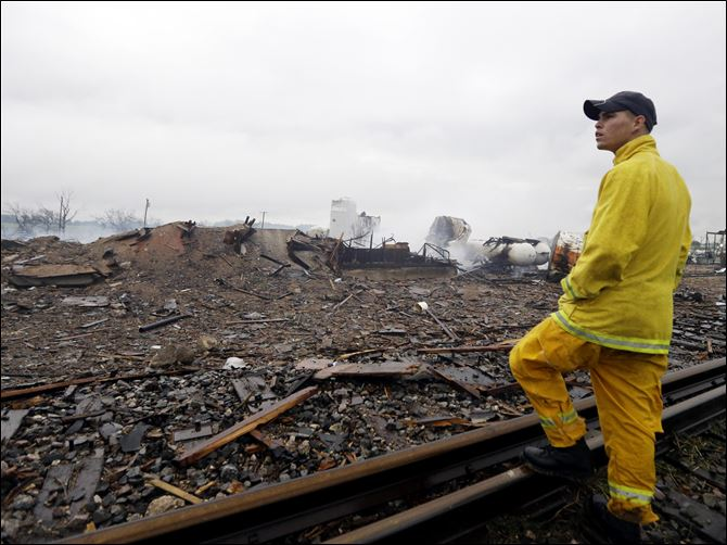 APTOPIX Plant Explosion Texas A firefighter stands on a rail line and surveys the remains of a fertilizer plant destroyed by an explosion in West, Texas, today.