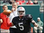 Braxton Miller passes during Ohio State's spring game under the watch of coach Urban Meyer. Miller, who will be a junior, is expected to be a Heisman Trophy favorite next season.