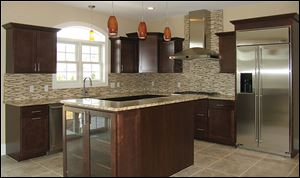 Crown molding tops the kitchen's maple cabinetry. The island and counters are topped with Santa Cecilia granite.