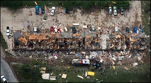 In this aerial photo, law enforcement and rescue personnel search the damage to an apartment complex from the explosion of the West Fertilizer plant on Thursday, April 18, 2013, in West, Texas. A massive explosion at the plant killed as many as 15 people and injured more than 160, officials said overnight. (AP Photo/Houston Chronicle, Smiley N. Pool)