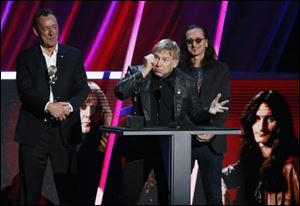 Alex Lifeson, center, Neil Peart, left, and Geddy Lee, right, of Rush accept their band's induction into the Rock and Roll Hall of Fame.