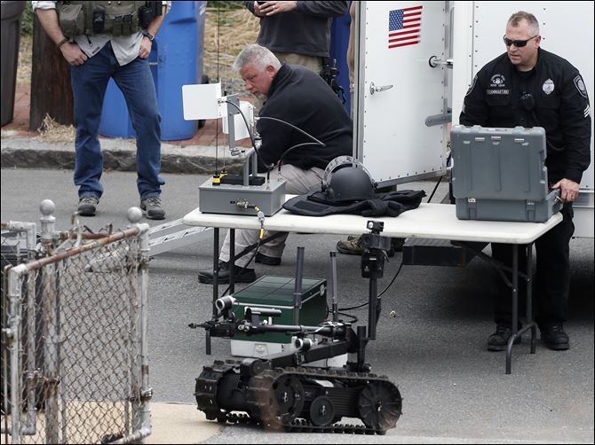 Police Converge Mass A member of the Cambridge police bomb squad, right, deploys a robot on Norfolk Street during a search for searching a suspect in the Boston Marathon bombings in Cambridge, Mass.. Two suspects in the Boston Marathon bombing killed an MIT police officer, injured a transit officer in a firefight and threw explosive devices at police during a getaway attempt in a long night of violence that left one of them dead and another still at large Friday, authorities said as the manhunt intensified for a young man described as a dangerous terrorist.