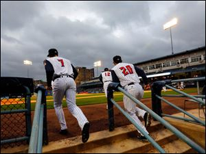 Toledo Mud Hens players take the field under a gloomy sky to play the Columbus Clippers.