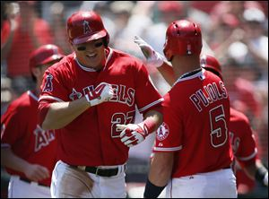 Los Angeles Angels' Mike Trout is congratulated by Albert Pujols, right, after hitting a grand slam off of Detroit Tigers starting pitcher Rick Porcello during the first inning Saturday in Anaheim, Calif.