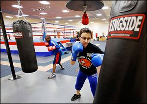 Four-time national Police Athletic League winner Monica Van Pelt, 17, works out at a punching bag during at the league's temporary facility at the former Riverside Hospital in North Toledo.