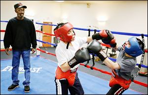 Carlos Velasquez, 12, left, spars with Emanuel Domiguez, 13, as coach Tony Talley keeps an eye on the action during a Police Athletic League workout.