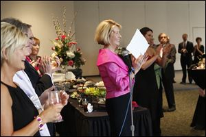 Event co-Chair Cindy Taylor, center, claps as she names off the Pink Tie Guys, men who have helped in the search for a cure for cancer, Saturday evening during the Pink Ribbon Gala at the SeaGate Convention Centre in downtown Toledo.