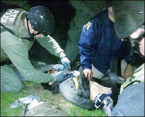 Agents check Dzhokhar Tsarnaev for explosives and give him medical attention after he was caught Friday in Watertown, Mass.