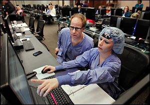 Operating-room man-ager Keith Hanf and Jenni Sheetz, both nurses, enter patient data from binders into a new computerized system at Mercy St. Vincent Medical Center.