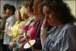LCCS case worker Denise Greenblatt, right, and other LCCS employees hold candles during the memorial.