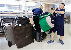 Jackson Sabo, 12, collects gear shortly after he and his family, including brother Ryker, 8, in back, and their mother, Kelly, reached Detroit Metropolitan Airport. The family from Rosemont, Minn., traveled to the Detroit area for a hockey tournament. Its bag of sticks did not arrive.