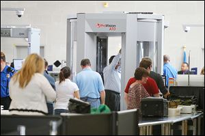 Travelers move through a security checkpoint in the McNamara Terminal of  Detroit Metropolitan Airport.