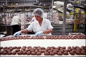 New technologies have led to a gradual workforce reduction over the years at the See's Candies factory in Los Angeles, California, but there's still plenty done by hand. Above, Bertha Ramos sorts through freshly-coated chocolate marshmallow eggs before they are sent off to be boxed and packaged.