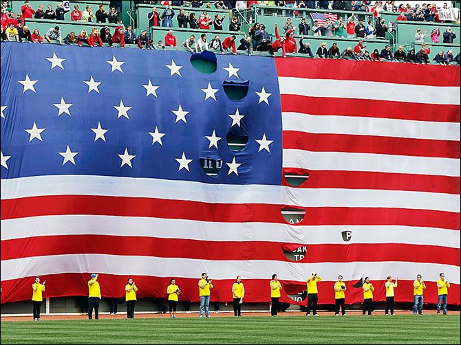 Boston Marathon volunteers stand beneath a giant flag on the outfield wall of Fenway Park during a tribute before a game between the Boston Red Sox and the Kansas City Royals on Saturday.