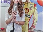 Bedford High student Megan McCormick with two of her favorite things: a microphone and a cardboard image of NASCAR racer Joey Logano, whom she met when she performed at a Virginia race.