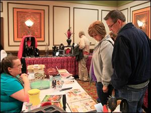 Heather Hughart, a consultant with The Pampered Chef ofNorth Ridgeville, Ohio, left, talks with Pam and Tom Dawson of Sylvania.