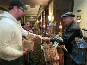 Jason Householder, left, his wife Trayci Householder of Findlay purchase a craft from Jack Catto of Dundee, Mich.