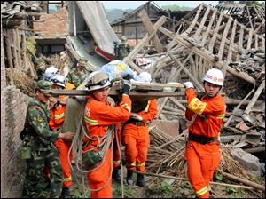Rescuers carry out an elderly paralyzed person from a collapsed house after an earthquake struck, in Qingren Township, Lushan County, Ya'an City, southwest China's Sichuan Province, Saturday.