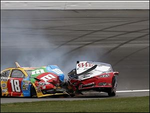 The cars of Kyle Busch (18) and Joey Logano got stuck together after a violent wreck that sent debris across the track.
