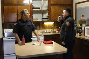Firefighters Mike Street, left, and Brian Lisowski chat in the temporary Fire Station No. 1 on Brint and McCord roads in Sylvania. The department is using the three-bedroom home, owned by Lourdes University, until construction of the new station in downtown Sylvania is complete.