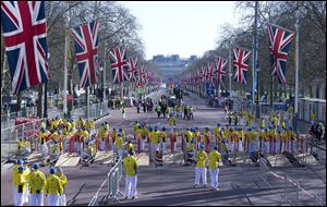Volunteers in bright yellow get ready prior to the London Marathon in the Mall in London, today. Security has been stepped up in London following the recent bombs at the Boston Marathon.