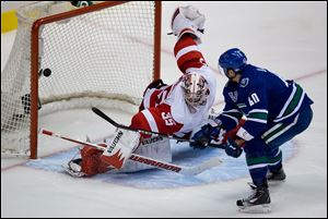 Vancouver Canucks' Maxim Lapierre scores the winning goal past Detroit Red Wings' goalie Jimmy Howard in a shootout Saturday in Vancouver, B.C.