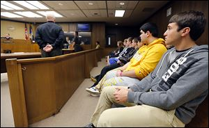 Anthony Wayne seniors Anthony Ulman, right, and Chris Wolfe, second from right, listen with other students from Pat Phillips' business law class as they visit Judge Michael Goulding's courtroom.