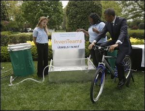 President Barack Obama pedals bicycle-powered emergency water-sanitation station for Payton Karr, 16, left, and Kiona Elliott, 18, center, to help demonstrate their invention.