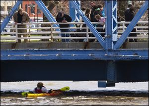 Spectators watch as a kayaker ducks underneath the blue bridge on the Grand River in downtown Grand Rapids, Mich., Sunday.