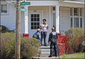 Angela Self talks to Dave Dustin, an FBI special agent, and Officer Melvin Haney of the Toledo Police Gang Unit at her home on Fernwood Avenue during their canvassing of the neighborhood.