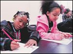Amaree Slaughter, left, and Yelena Castillo write stories as part of the Farmhouse at Wildwood Metropark in Toledo as part of the Women's Initiative.