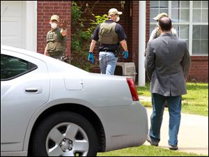 An FBI agent stops homeowner James E. Dutschke from approaching his home today in Tupelo, Miss. The agents began to search his home in connection with the ricin letters sent to  Sen. Roger Wicker and President Barack Obama.